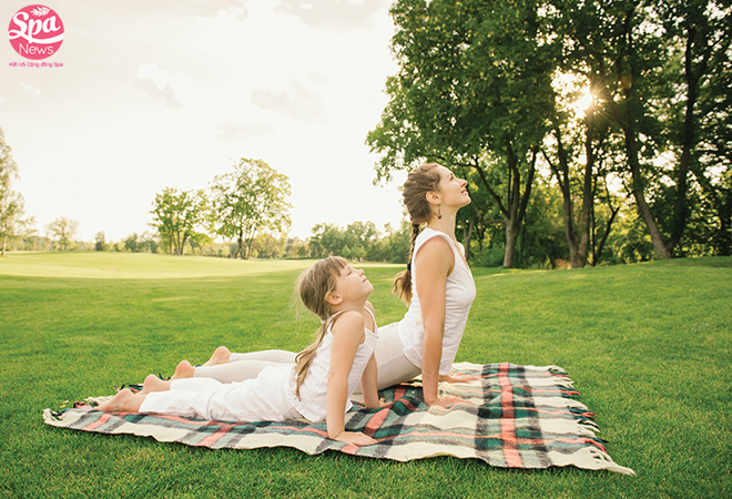 Mother and daughter doing exercise outdoors. Family healthy lifestyle concept.